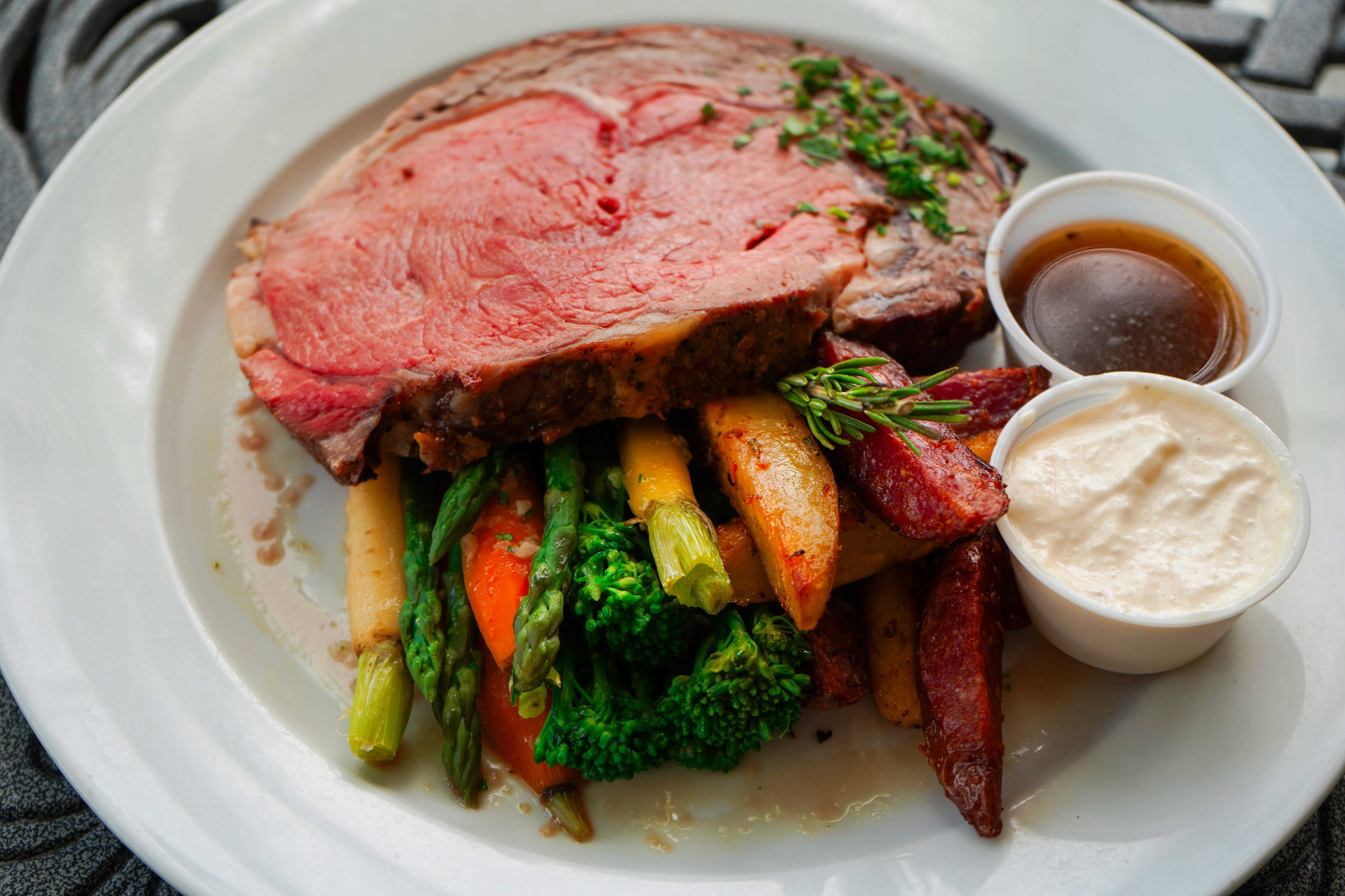 prime rib on pile of vegetables with sauces