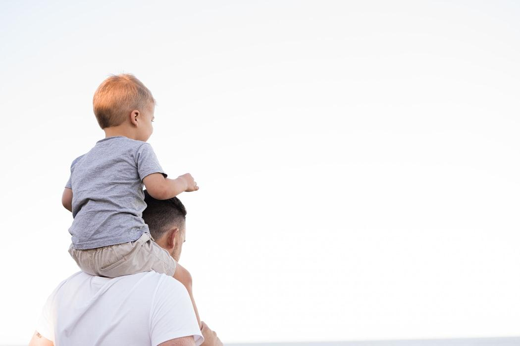 dad holding child on his shoulders